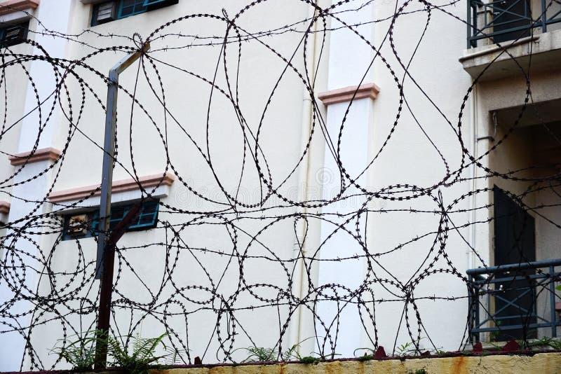 Cavo pungente aggrovigliato del rasoio in cima alla parete della barriera in Sud-est asiatico immagine stock libera da diritti