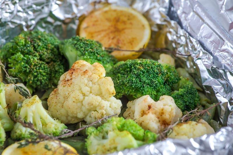 Cavolfiore e broccoli con il limone, le spezie ed il timo al forno in stagnola nel forno immagine stock libera da diritti
