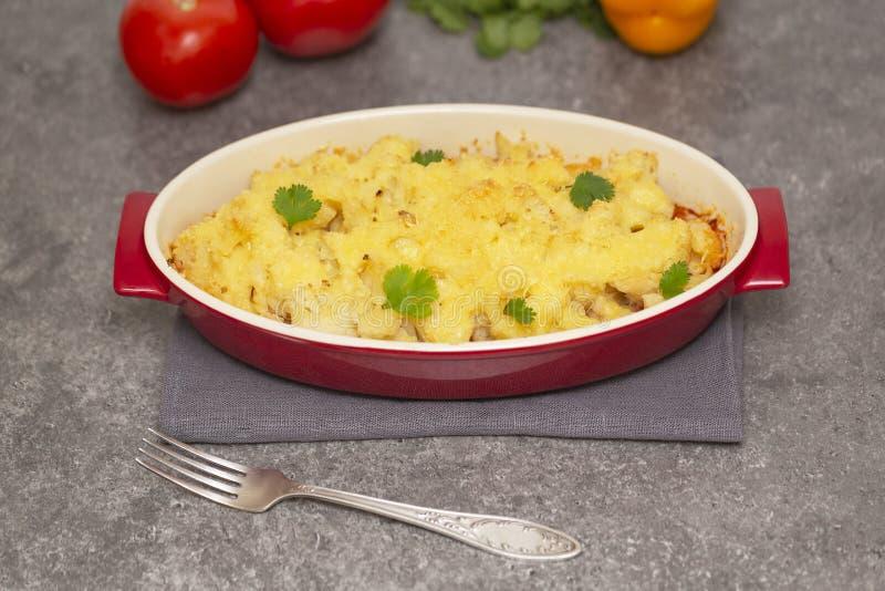 Cavolfiore, pomodori e gratin del formaggio nel piatto bollente fotografia stock libera da diritti