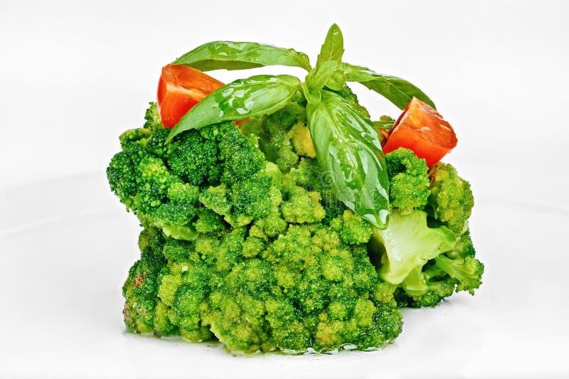 Cavolo dei broccoli cucinato con i pomodori e le foglie del basilico fotografie stock libere da diritti