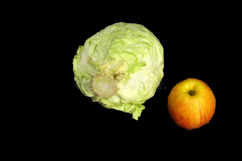 Cavolo fresco e una mela deliziosa su un fondo nero immagine stock