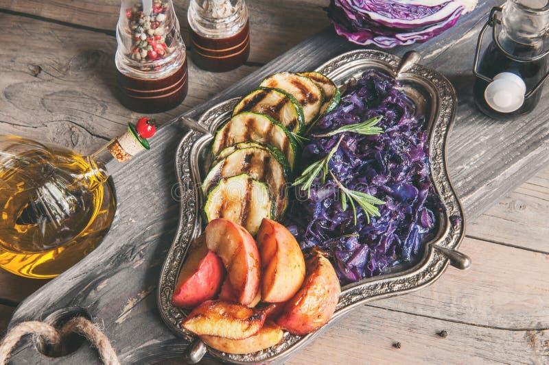 Cavolo rosso brasato con i bei pezzi arrostiti delle mele e delle cipolle, condendo con il limone e l'olio d'oliva su un bello pi fotografia stock libera da diritti