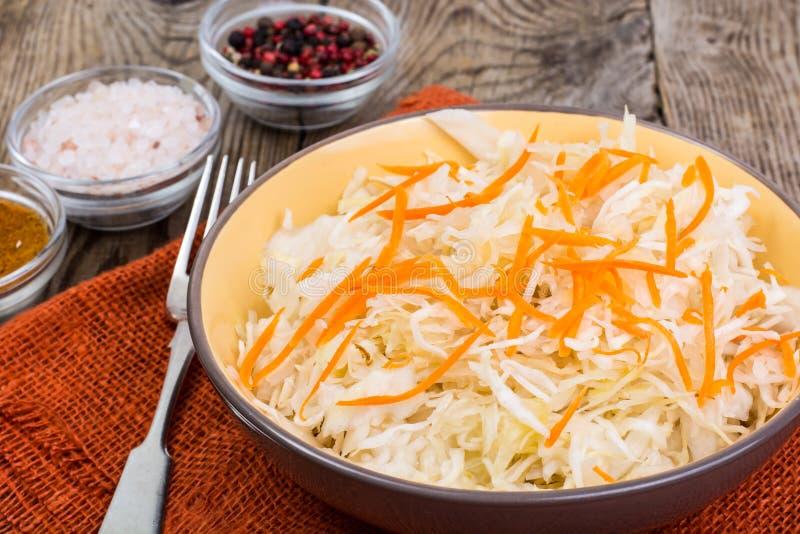 Cavolo salato sul piatto sui precedenti della tavola di legno immagine stock libera da diritti