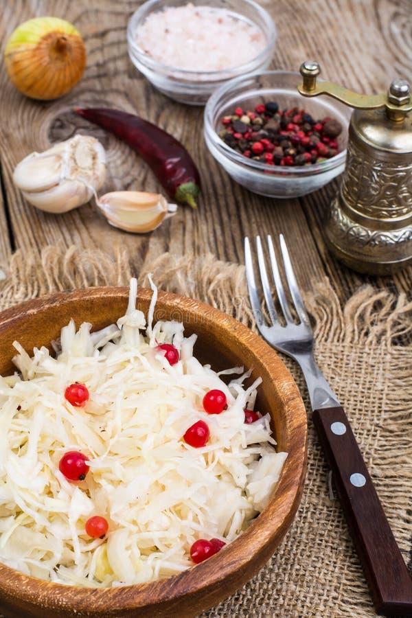 Cavolo salato sul piatto sui precedenti della tavola di legno immagini stock