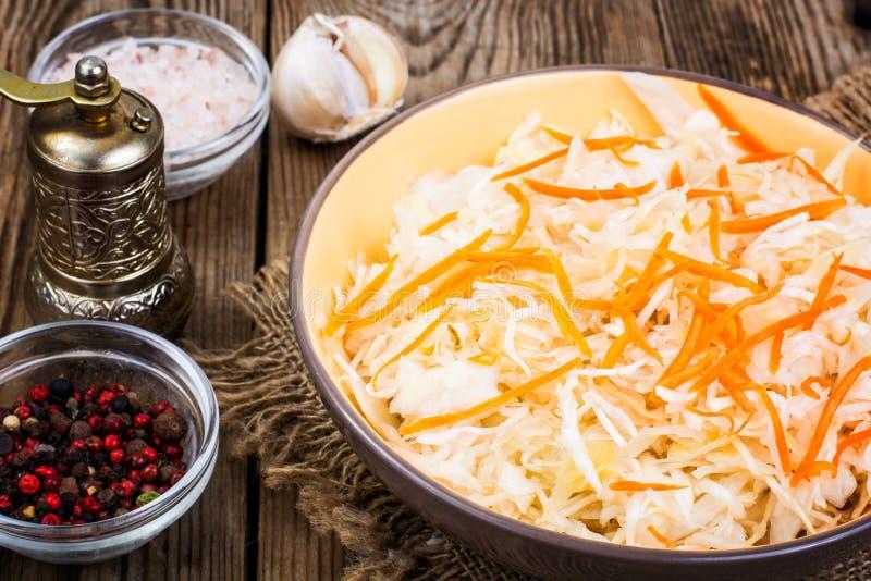 Cavolo salato sul piatto sui precedenti della tavola di legno immagini stock libere da diritti