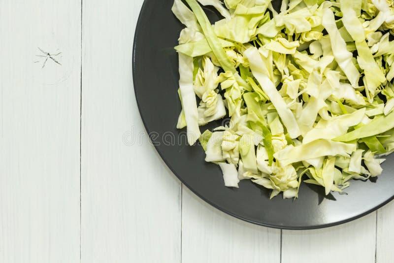 Cavolo verde fresco su una banda nera su una tavola bianca Spazio per testo fotografie stock