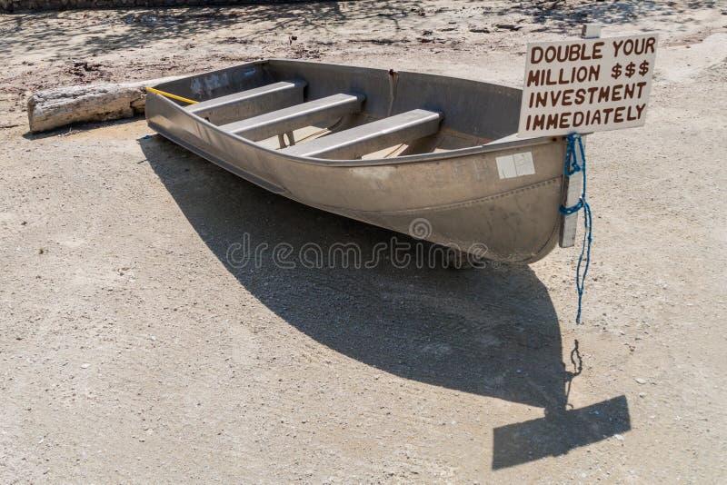 CAYE-BREEUWIJZER, BELIZE - MAART 2, 2016: De kleine boot met een teken verdubbelt uw investering bij Caye-Breeuwijzereiland, Beli stock fotografie