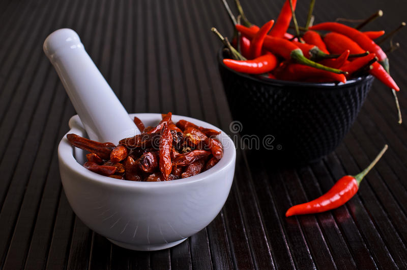 Cayenne pepper. The pods dry red Cayenne pepper in a white mortar on black surface royalty free stock image