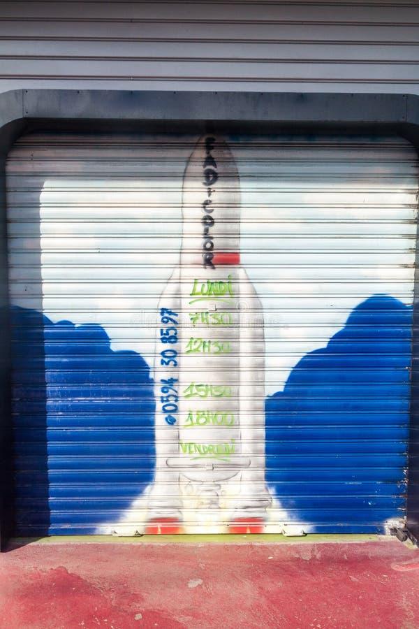 CAYENNEPFEFFER, FRANZÖSISCH-GUAYANA - 1. AUGUST 2015: Rocket Ariane 5 malte auf einem Eingang zur Garage in der Mitte von Cayenne lizenzfreie stockfotografie