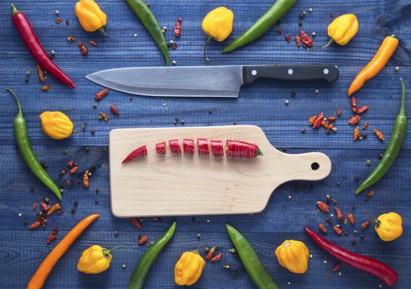 Cayennepfeffer-Paprikapfeffer auf Schneidebrett mit verschiedenen Pfeffern ganz herum lizenzfreies stockfoto