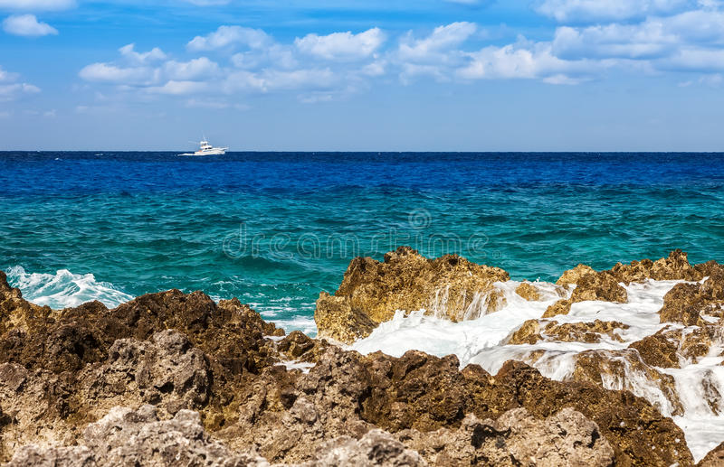Cayman Islands. Fishing boat on the Caribbean along the rocky shoreline of Grand Cayman, Cayman Islands royalty free stock image