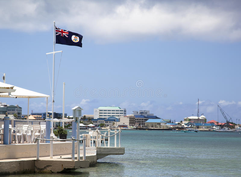Cayman Islands. Flag with George Town in a background (Grand Cayman island royalty free stock image