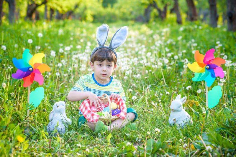 Caza del niño pequeño para el huevo de Pascua en jardín de la primavera el día de Pascua Pequeño niño lindo con el conejito tradi imagen de archivo