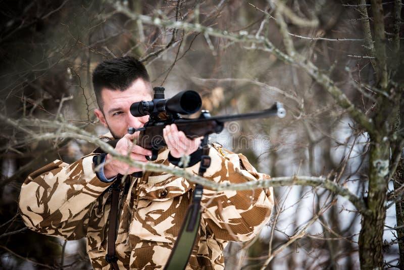 Caza, ejército, concepto militar - francotirador que sostiene el rifle y que tiene como objetivo la blanco en el bosque durante l fotos de archivo