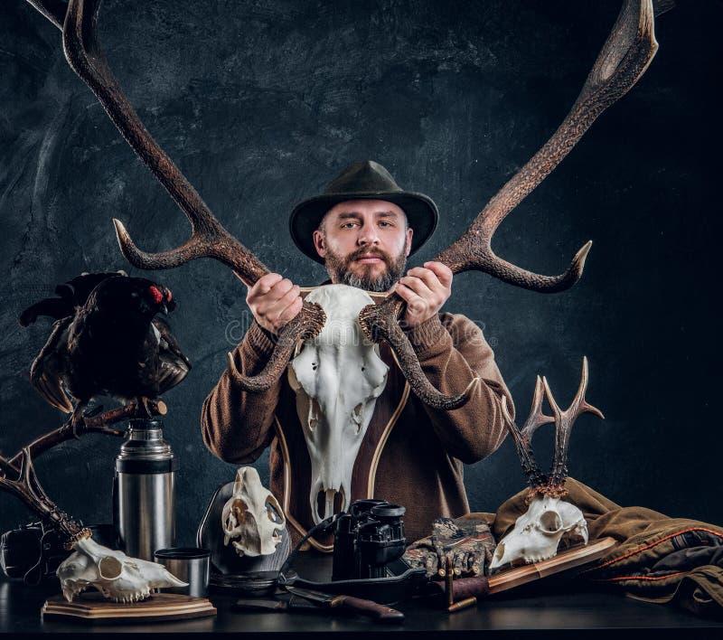 Cazador barbudo maduro en el sombrero que sostiene un cráneo grande de los ciervos mientras que se coloca al lado de una tabla co imagen de archivo