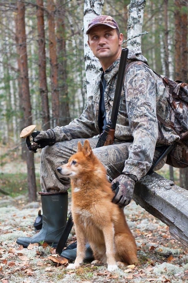 Cazador con el perro que descansa durante la caza imagenes de archivo