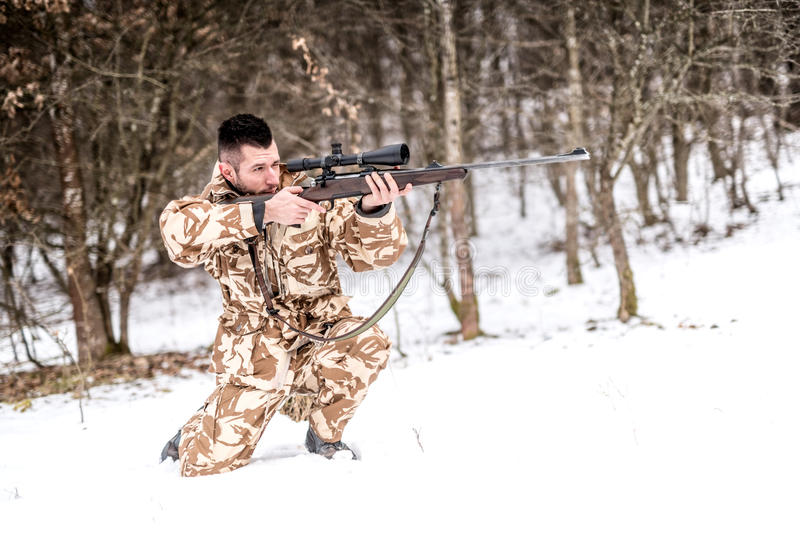 Cazador con el rifle de francotirador que apunta y que tira durante invierno foto de archivo
