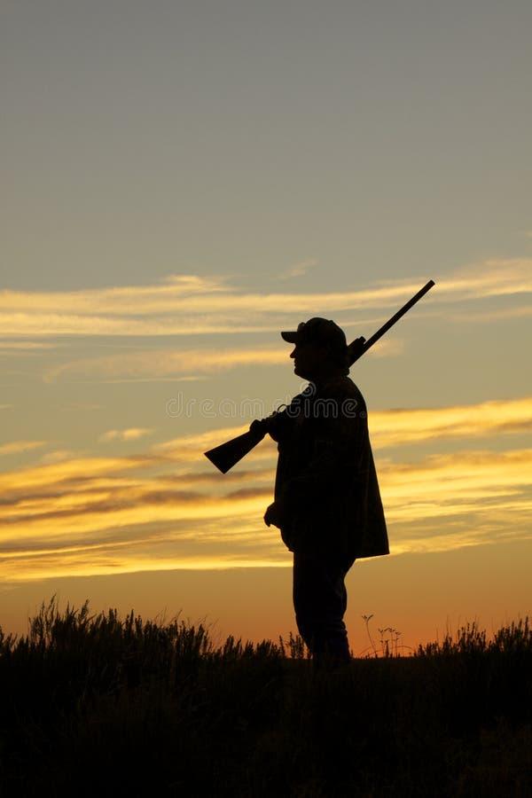 Cazador con la escopeta en puesta del sol imagen de archivo libre de regalías