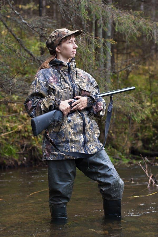 Cazador de la mujer con el arma en el pequeño río en el bosque foto de archivo