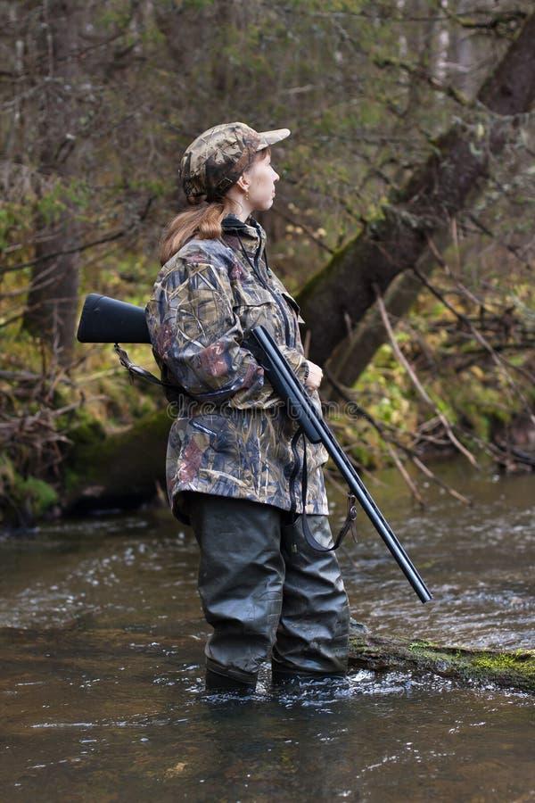 Cazador de la mujer que mira hacia fuera para la presa en el río del bosque imagen de archivo
