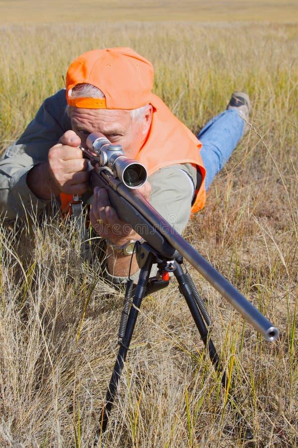 Cazador del rifle en la posición propensa