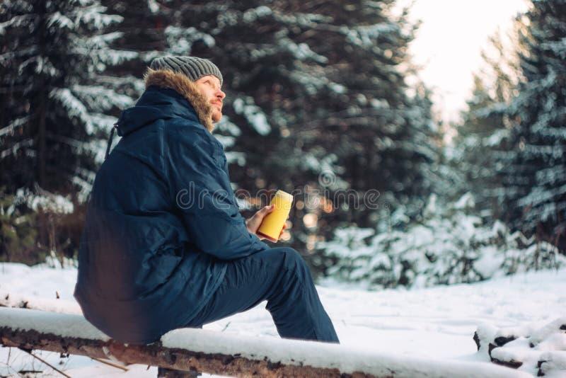 Cazador del silvicultor del viajero del hombre en el bosque del invierno que se sienta en árbol caido foto de archivo