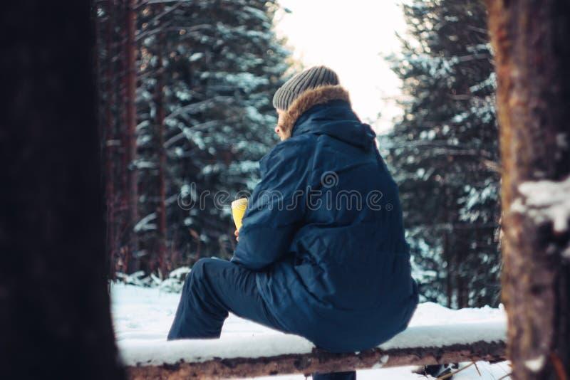 Cazador del silvicultor del viajero del hombre en el bosque del invierno que se sienta en árbol caido fotografía de archivo