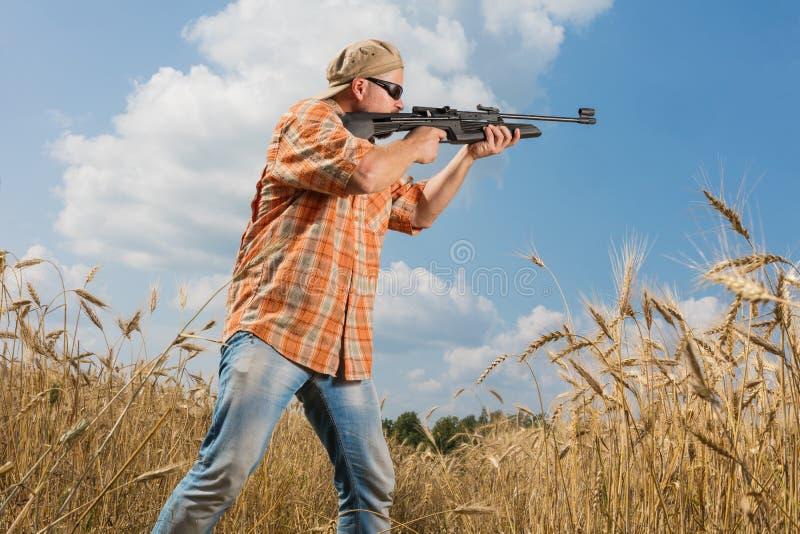 Cazador en el casquillo y las gafas de sol que apuntan un arma al campo fotografía de archivo libre de regalías