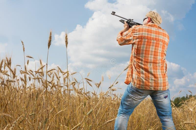 Cazador en el casquillo y las gafas de sol que apuntan un arma al campo imagen de archivo