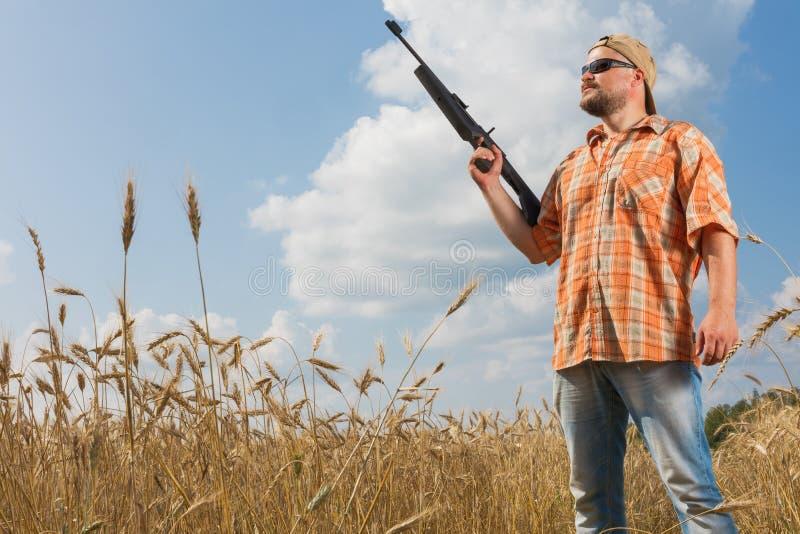 Cazador en el casquillo y las gafas de sol que apuntan un arma al campo fotos de archivo