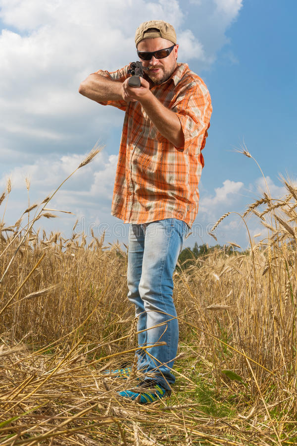 Cazador en el casquillo y las gafas de sol que apuntan un arma al campo imágenes de archivo libres de regalías
