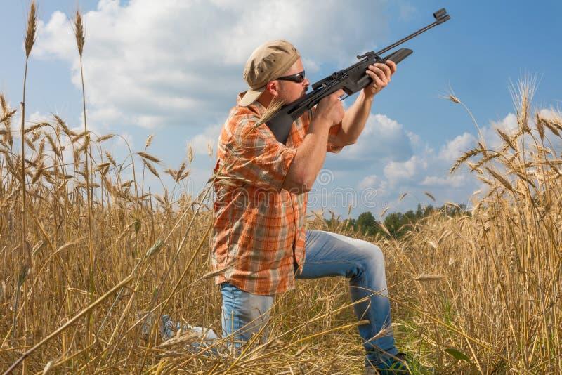 Cazador en el casquillo y las gafas de sol que apuntan un arma al campo fotos de archivo libres de regalías