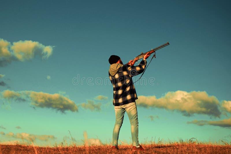 Cazador en la temporada de caza de la ca?da Cazador con el arma de la escopeta en caza Skeet Shooting imagenes de archivo