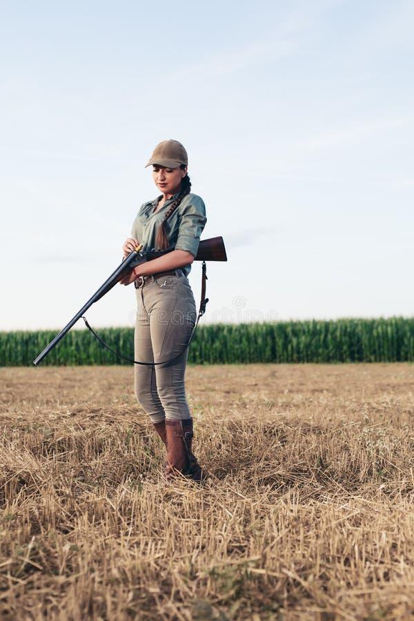 Cazador femenino atractivo que recarga su rifle fotos de archivo libres de regalías