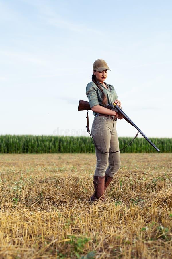 Cazador femenino atractivo que recarga su rifle imagenes de archivo