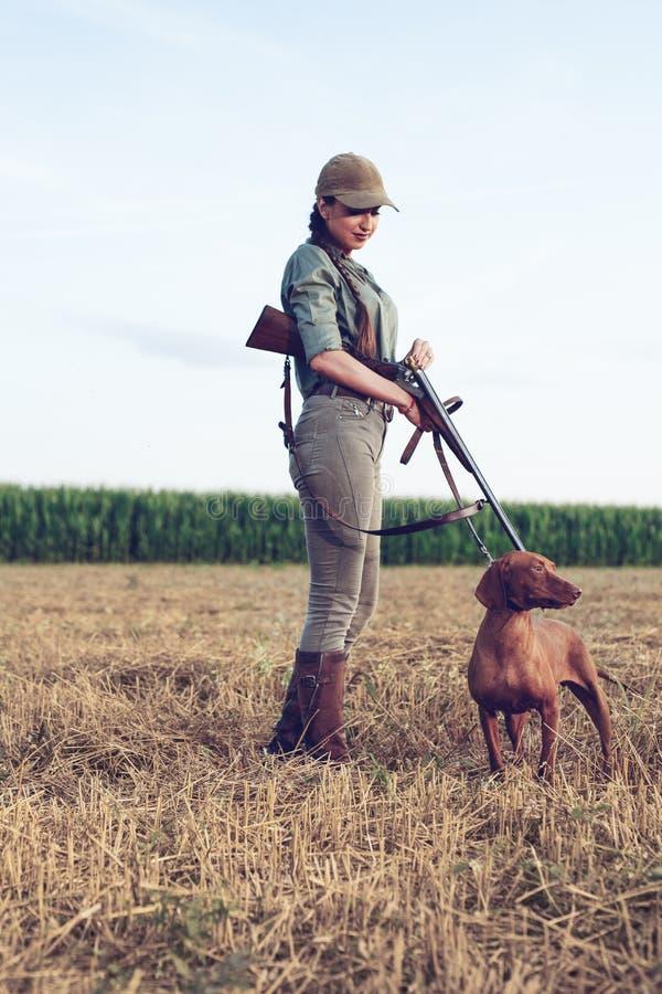 Cazador femenino atractivo que recarga su rifle foto de archivo