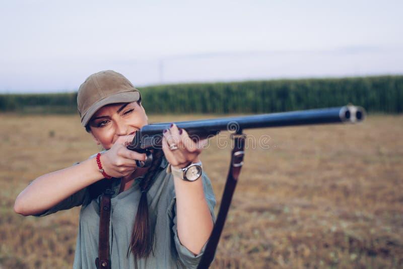 Cazador femenino que apunta con su arma fotografía de archivo libre de regalías