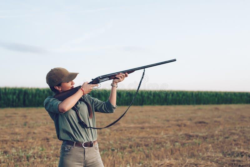 Cazador femenino que apunta con su arma foto de archivo