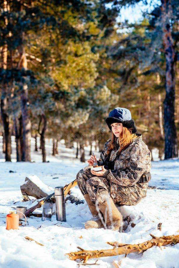 Cazador femenino que prepara la comida con un mechero de gas portátil en un triunfo imagen de archivo