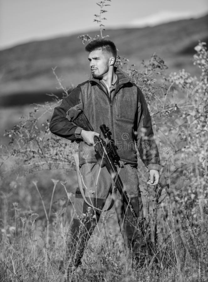 Cazador furtivo brutal del cazador Cazador furtivo barbudo del cazador que busca a la v?ctima Cazador furtivo con el rifle en el  imagen de archivo