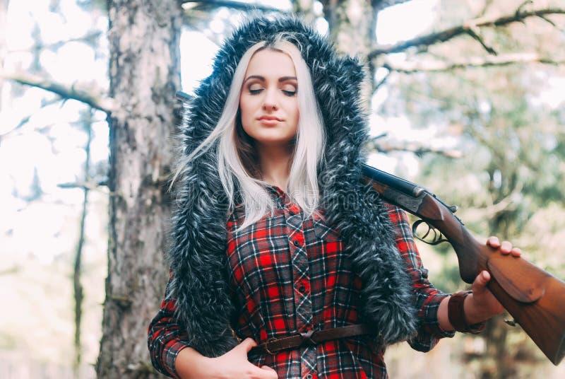 Cazador hermoso de la mujer en bosque con el arma imagenes de archivo