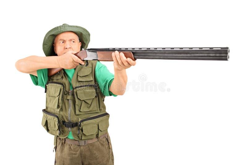 Cazador maduro que apunta con un rifle fotografía de archivo libre de regalías