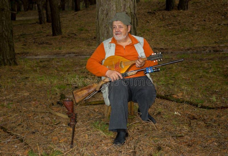 Cazador mayor sonriente que descansa en bosque de la tarde foto de archivo libre de regalías