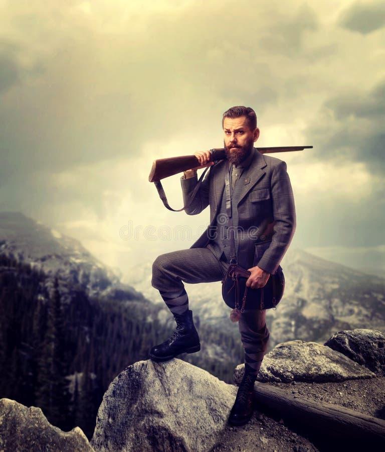 Cazador pasado de moda barbudo en montaña rocosa imagen de archivo