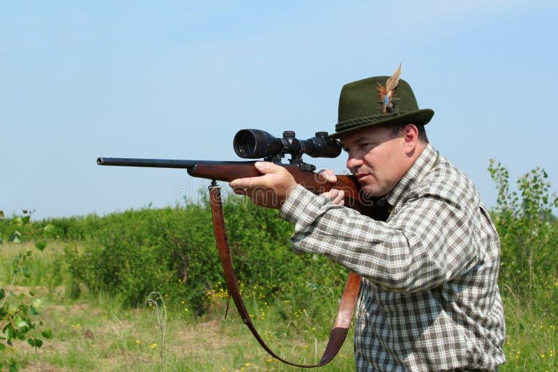 Cazador que apunta con el rifle fotografía de archivo