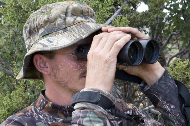 Cazador que mira a través de los prismáticos foto de archivo libre de regalías