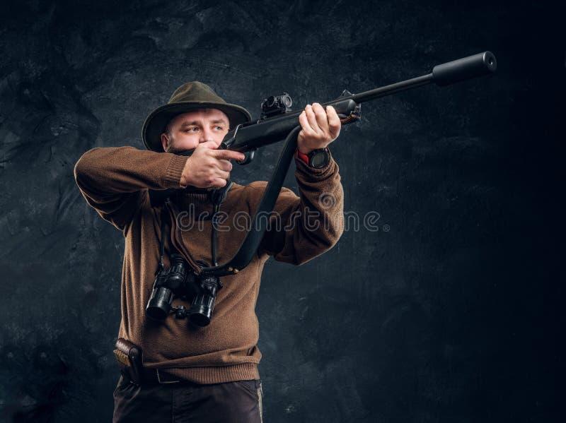 Cazador que sostiene un rifle y que tiene como objetivo su blanco o presa Foto del estudio contra fondo oscuro de la pared imagenes de archivo