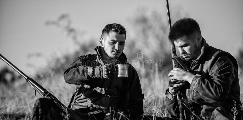 Cazadores con los rifles que se relajan en el ambiente de la naturaleza Los amigos de los cazadores disfrutan de ocio Caza con oc foto de archivo libre de regalías