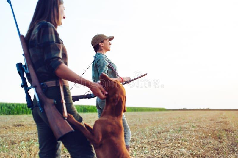 Cazadores de las mujeres con el perro de caza foto de archivo libre de regalías