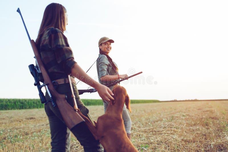 Cazadores de las mujeres con el perro de caza fotos de archivo